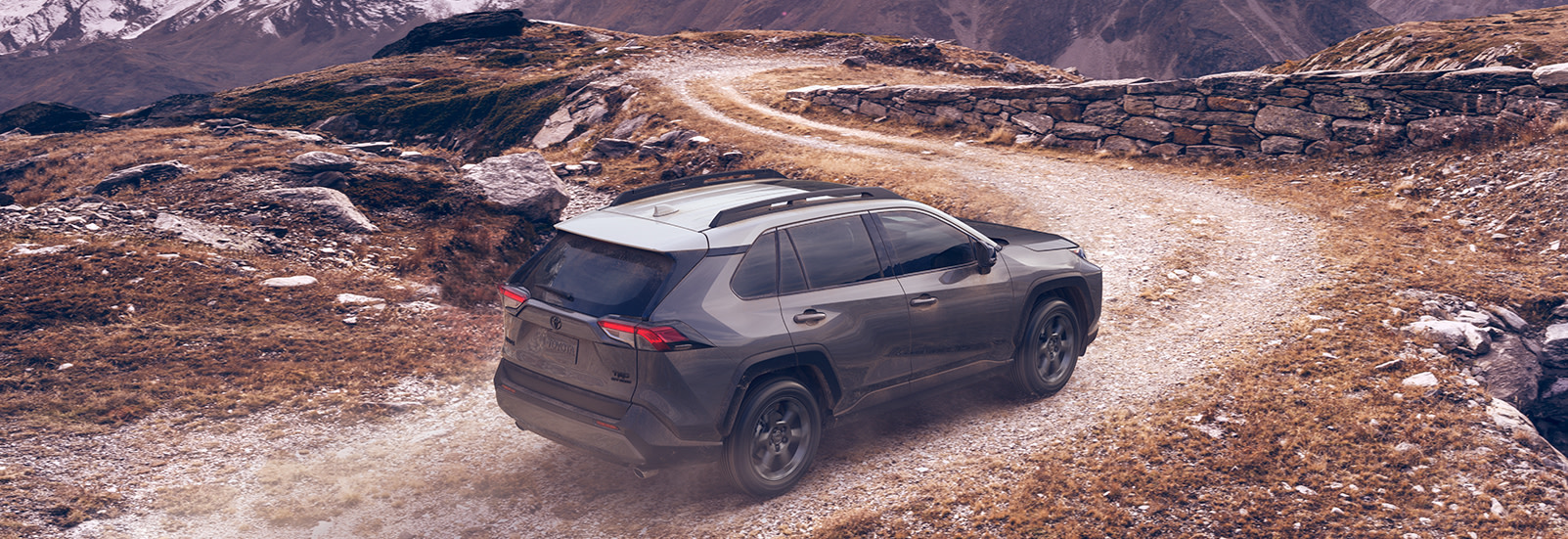 Performance features of the 2020 Toyota RAV4 & RAV4 Hybrid at Tri County Toyota | Grey 2020 RAV4 driving on rocky road