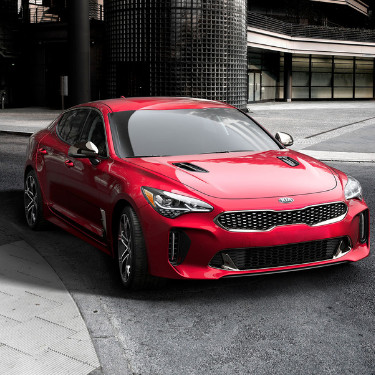 The front angle of a shiny red 2019 Kia Stinger as it makes a right turn on an empty city street in front of a big industrial complex
