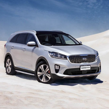 The front passenger side of a silver 2019 Kia Sorento parked on white sandy dunes with a clear blue sky overhead