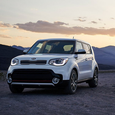 The front driver side of a white 2019 Kia Soul parked on a dirt path as the automatic headlights turn on with the sun setting behind a mountain range in the background