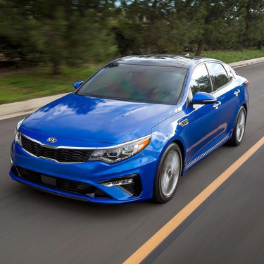 An angle of the front driver side of a shiny blue 2019 Kia Optima as it speeds down an open road with green trees lining the road