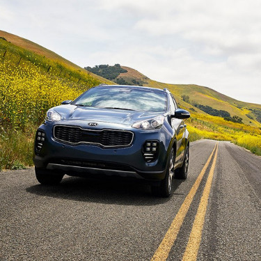A view of the front of a steel blue 2019 Kia Sportage SUV as it casually drives down an empty country road through foothills cover with yellow dandelions