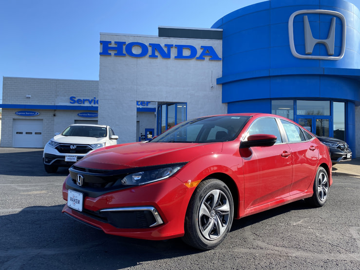 Picture of a red Honda Civic parked in front of a blue and gray Honda dealership