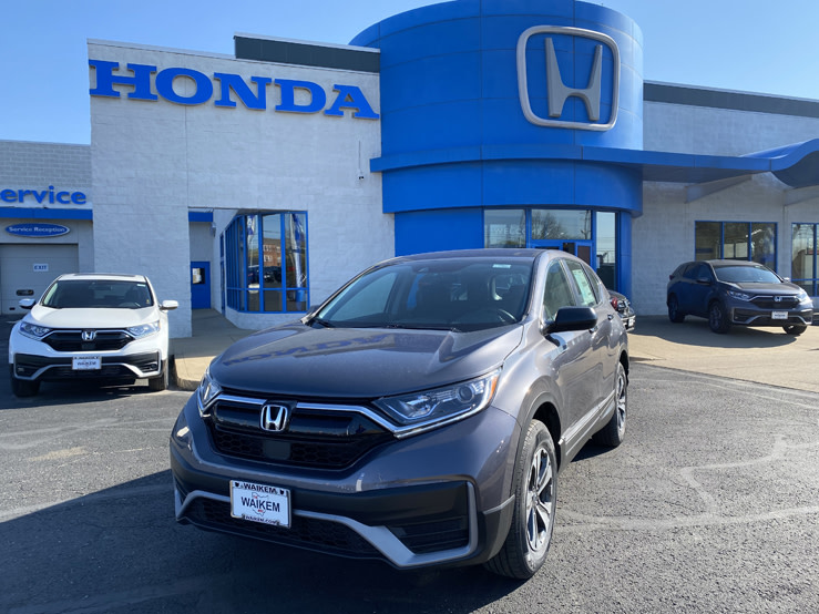 Picture of a gray Honda CR-V parked in front of a blue and gray Honda dealership