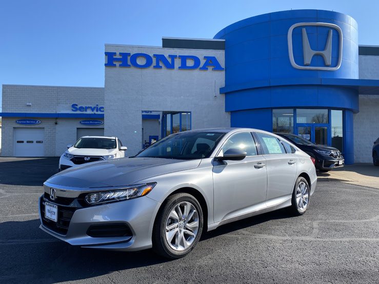 Picture of silver Honda Accord sedan parked in front of a gray and blue building with a Honda logo on it