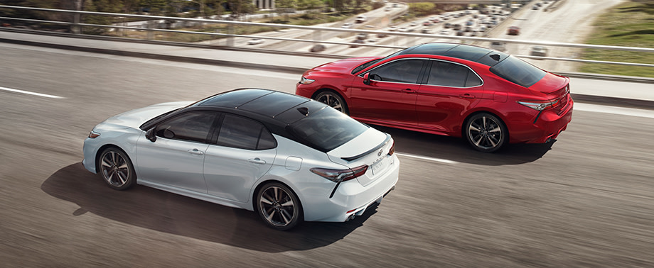 Team Toyota of Glen Mills is a Toyota Dealership near Kennett Square PA   Two 2020 Toyota Camry vehicles racing on city road